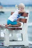 Kleines Mädchen auf einer Bank   Lizenzfreies Stockbild