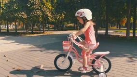 Kleines Mädchen auf einer rosa Fahrradsommertätigkeit stock video footage