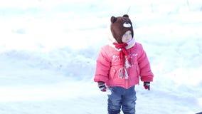 Kleines Mädchen auf einer schneebedeckten Straße stock footage
