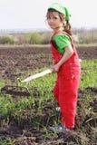 Kleines Mädchen auf Feld mit Hackehilfsmittel Stockfotografie