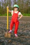 Kleines Mädchen auf Feld mit Schaufel Stockfoto