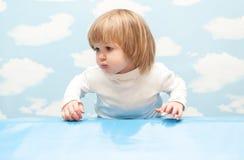 Kleines Mädchen auf Hintergrund des blauen Himmels Stockfoto