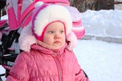 Kleines Mädchen auf Schneehintergrund und Kinderwagen. Lizenzfreie Stockbilder