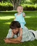 kleines Mädchen auf Schultern des Vatis Stockfotografie
