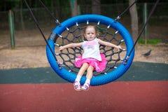 Kleines Mädchen auf Schwingen an einem Vergnügungspark Stockfotos