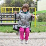 Kleines Mädchen auf Schwingen am Spielplatz Stockfoto