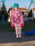 Kleines Mädchen auf Schwingen am Spielplatz Stockfotos