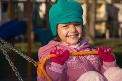 Kleines Mädchen auf Schwingen am Spielplatz Stockbilder