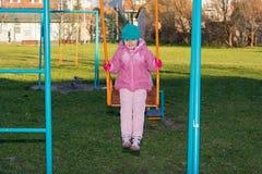 Kleines Mädchen auf Schwingen am Spielplatz Stockfotografie