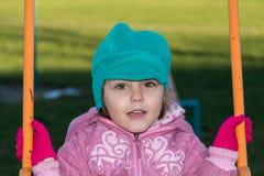 Kleines Mädchen auf Schwingen am Spielplatz Stockbild