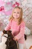 Kleines Mädchen auf Spielzeugpferd im Weihnachtsinnenraum stockbild