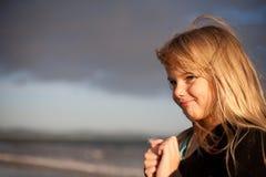 Kleines Mädchen auf Strand mit Löwenzahnblume Lizenzfreies Stockbild