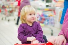 Kleines Mädchen auf Wagen im Supermarkt mit Mutter stockfotografie