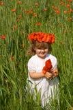 Kleines Mädchen auf Weizenfeld mit Mohnblumen Stockfoto