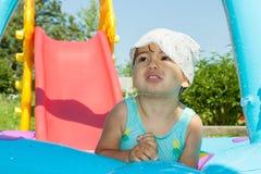 Kleines Mädchen badet im Pool Stockfotografie