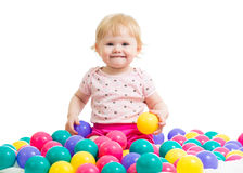 Kleines Mädchen in Ballgrube woth färbte Bälle Stockfotos