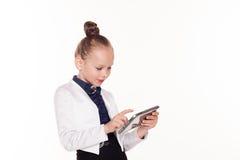 Kleines Mädchen betrachtet Geschäft Damentablet-computer lizenzfreie stockfotos