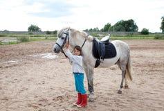 Kleines Mädchen betriebsbereit zu einer Pferderueckenreitlektion Stockbilder