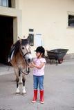 Kleines Mädchen betriebsbereit zu einer Pferderueckenreitlektion Lizenzfreie Stockfotos