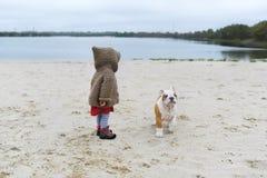 Kleines Mädchen bildet ihren Welpen am Strand im Herbst aus Kinderspiele mit ihrer kleinen Bulldogge Lizenzfreie Stockbilder