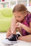 Kleines Mädchen bindet Schuhe Stockbilder