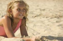 kleines Mädchen blond auf dem Strand, Sandporträt Stockbilder