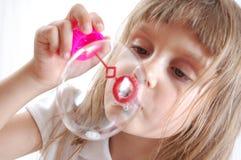 Kleines Mädchen brennt große Luftblase durch Stockfotos