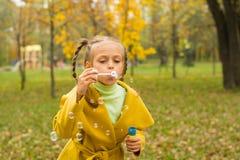 Kleines Mädchen brennt Seifenblasen im Park durch Stockfotografie