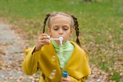 Kleines Mädchen brennt Seifenblasen im Park durch Stockfoto