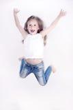 Kleines Mädchen, das über den weißen Hintergrund springt Stockfotos