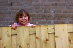 Kleines Mädchen, das über den Zaun späht Lizenzfreie Stockbilder