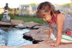 Kleines Mädchen, das über Teich sich lehnt Stockfotografie