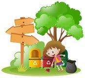 Kleines Mädchen, das Abfall im Garten aufhebt lizenzfreie abbildung