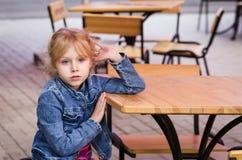 Kleines Mädchen, das allein an einem Tabellencafé sitzt Lizenzfreies Stockbild