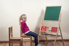 Kleines Mädchen, das allein vor einer Tafel sitzt. Lizenzfreies Stockfoto