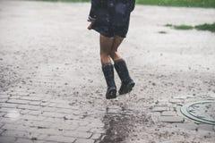 Kleines Mädchen, das alleinaußenseite im schlechten Wetter spielt lizenzfreies stockfoto