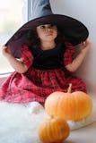 Kleines Mädchen, das als Hexe für Halloween sitzt auf dem Fenster trägt lizenzfreies stockbild