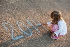 Kleines Mädchen, das 2014 auf Asphalt schreibt Lizenzfreie Stockfotos