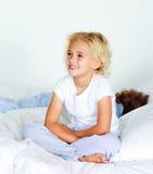 Kleines Mädchen, das auf Bett bevor dem Schlafen sitzt Stockbild