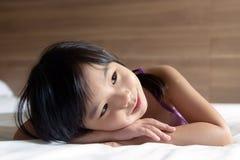 Kleines Mädchen, das auf Bett legt Stockbilder