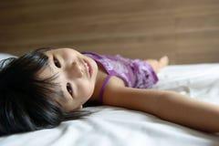 Kleines Mädchen, das auf Bett legt Lizenzfreie Stockbilder