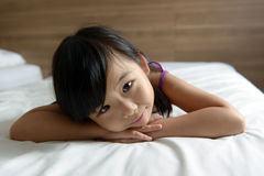 Kleines Mädchen, das auf Bett legt Lizenzfreies Stockbild