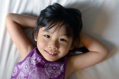 Kleines Mädchen, das auf Bett legt Stockfotografie