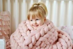 Kleines Mädchen, das auf Bett mit einem gestrickten riesigen Plaid sitzt Stockfotos