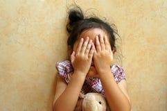 Kleines Mädchen, das auf Boden, Abschluss ihr Gesicht legt stockfotos