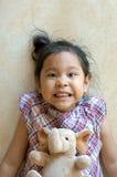 Kleines Mädchen, das auf Boden mit Elefantpuppe legt stockfoto