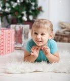 Kleines Mädchen, das auf Boden nahe Weihnachtsbaum liegt Stockfotografie