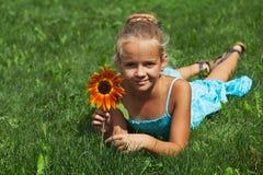 Kleines Mädchen, das auf das Gras mit einer Blume legt Stockbild