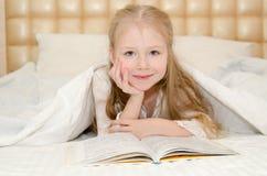 Kleines Mädchen, das auf dem Bett liegt und ein Buch liest Stockfoto