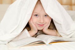 Kleines Mädchen, das auf dem Bett liegt und ein Buch liest Stockfotos